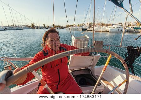 Man skipper at the helm controls of a sailing yacht.