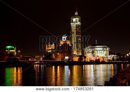 Night panorama of the Moscow House of Music is reflected in the Moscow river, Russia.