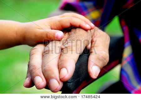 little girl holding a handicapped man`s hand