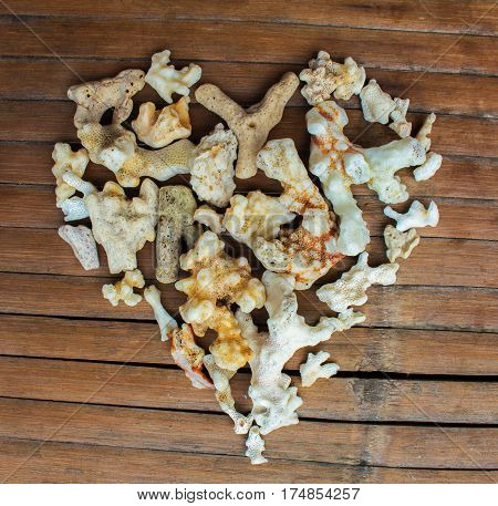 Heart from white corals on wooden background. Handmade love decor from beach finding. Multicolored ornament for Valentine Day greeting. Nature care concept. Seaside decor. Marine heart grungy backdrop