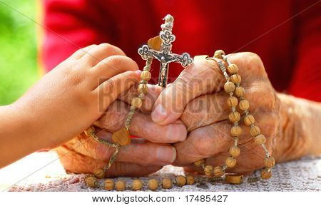 child hand holding old catholic woman hand who holds rosary