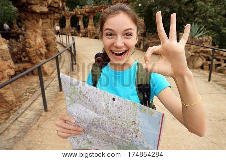 Hiking. Enthusiastic tourist shows okay gesture. Young happy girl using travel map during her hike. Travel in Spain.