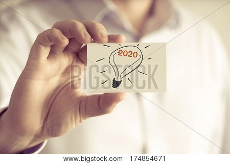 Businessman Holding Message Card With Light Bulb Symbol And Text 2020