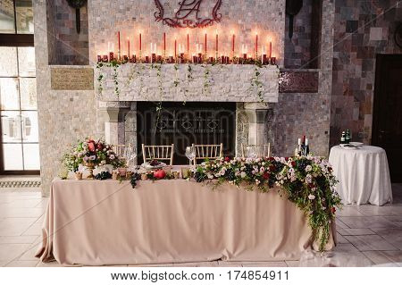 Wedding table decoration for the fiance and fiancee with the red coat of arms and lighted candles