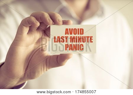Businessman Holding Avoid Last Minute Panic Message Card
