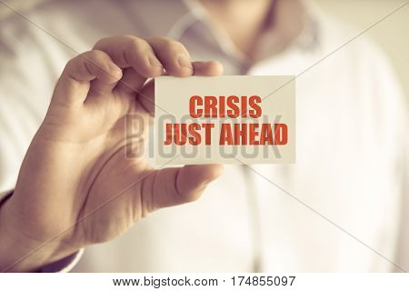 Businessman Holding Crisis Just Ahead Message Card