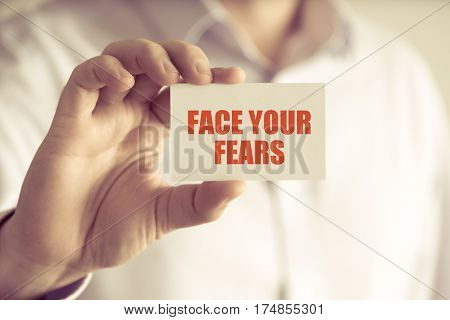 Businessman Holding Face Your Fears Message Card