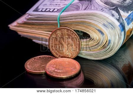 Us Roll Dollar With Coin Isolated On Black.