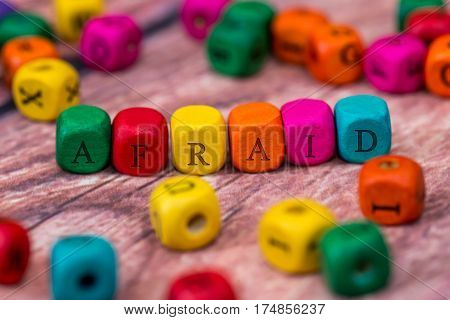 Afraid - Word Created With Colored Wooden Cubes On Desk.