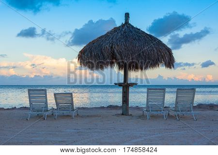 Sunlounge chairs and umbrella on the sunset beach in Marathon Key Florida Keys USA