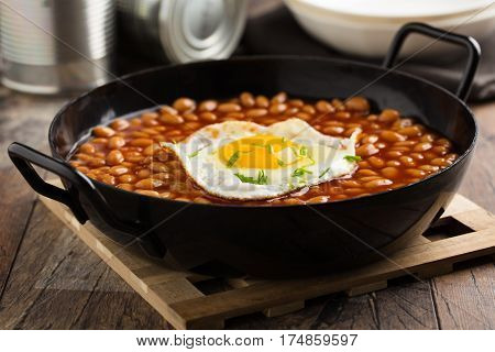 Baked beans with fried egg served in a pan.