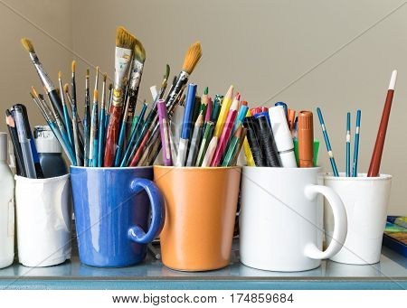 Close up of different used paint brushes sharpened colored pencils pens and markers on colored mugs over blue table and beige background