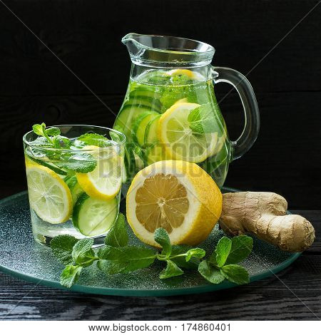 Water Sassi. Vitaminized cleansing water with lemon cucumber ginger mint and ice in a pitcher and a glass on a metal tray. The concept of dietary and vegetarian nutrition. Square image