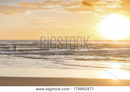 Surfer in the ocean waves at sunrise. Surfers Paradise, Gold Coast.