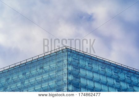 Modern glossy facade of building against of the cloudy sky. Multilayer facade system of a high-rise building. Spider facade fixing system. Symmetry composition