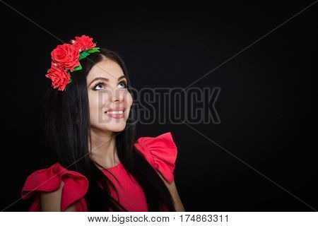 Woman with long black hair and a wreath with red flowers on a dark background smiles and looks away. Close-up. Space for text