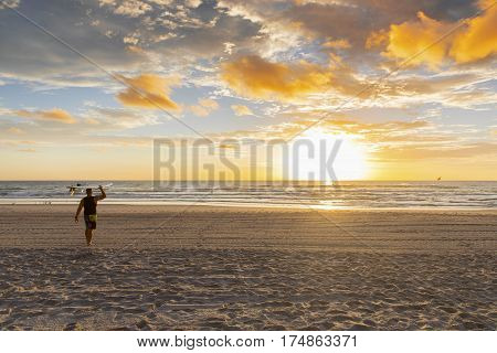Surfer walking on the beach with surfboard on head at sunrise. Surfers Paradise, Gold Coast.