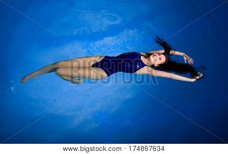 Young woman swimmer in blue pool