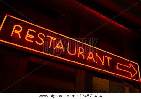 Litted restaurant sign with arrow made of red fluorescent light in the wall with dark background