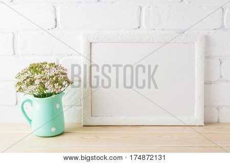 White landscape frame mockup with wild very soft pink flowers in mint pitcher near painted brick wall. Empty frame mock up for presentation design. Template framing for modern art.