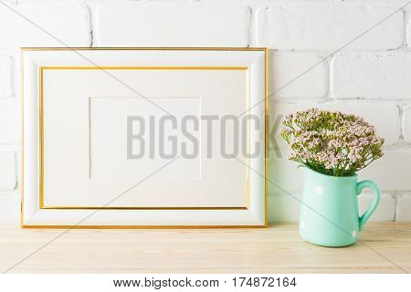 Gold decorated landscape frame mockup with very soft pink flowers in mint pitcher vase near painted brick wall. Empty frame mock up for presentation design. Template framing for modern art.