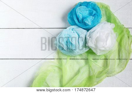 Drape in the form rose of colored gauze on white wooden background. Used in design for decor