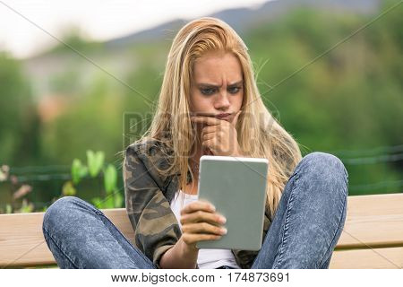 Worried Young Woman Checking Social Media On Tablet