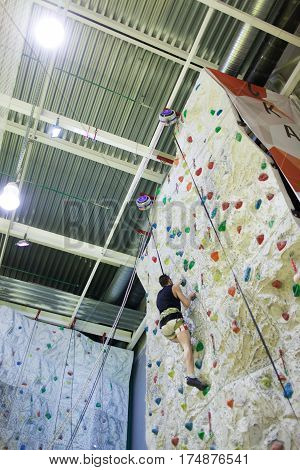 Young Athletic Guy Climbing Indoor At Artificial Wall