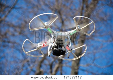 drone with camera hovering in trees with blue sky