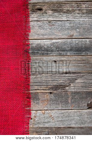 red frayed burlap border on weathered wood