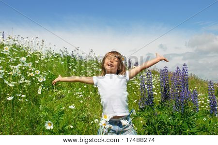 Little girl standing on a meadow in a field of beautiful flower and has fun