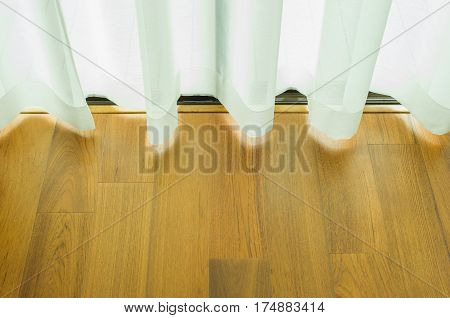 Curtain that shade sunlight on sliding doors with wooden floor. Backdrop curtains