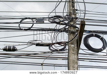 High voltage power pole with wires tangled,Wire and cable clutter. Potential danger from a mess of wires , Electric pole with electric wire tangled,very messy electricity or telephone pole.