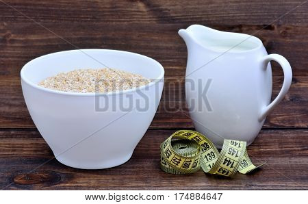 Bowl with oatmeal and pitcher with milk and centimeter on wooden background
