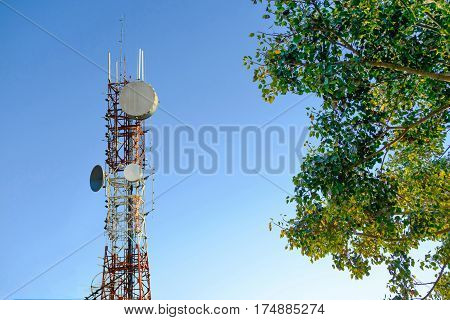 Mobile Phone Communication Antenna Tower With Cloud On Center Blue Sky Background And Tree