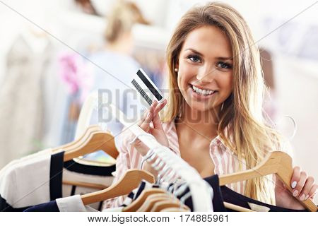 Happy woman shopping for clothes with credit card
