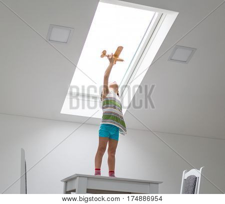 Happy child holding wooden airplane at home standing under roof window having dreams