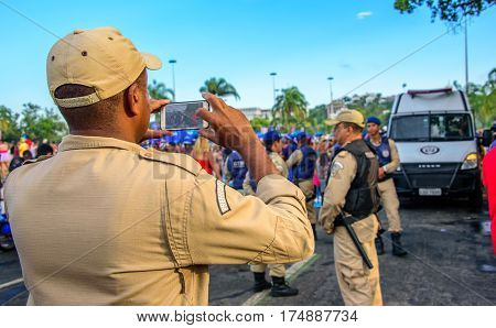 RIO DE JANEIRO, BRAZIL - FEBRUARY 28, 2017: Back of the policeman taking pictures of costume people at Bloco Orquestra Voadora in Flamengo Park on the background of Sugarloaf Mountain, Carnaval 2017
