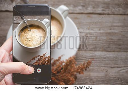 Taking a photo by Finger Pressing on Smartphone for Photograph Close up Hot Coffee on wooden with Copy Space in Chill and Relax Concept Image for Coffee Advertise or Social Media with Drink Concept