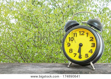 Closeup black and yellow alarm clock for decorate show half past six or 6:30 a.m. on old brown wood desk on green leaves in the park textured background