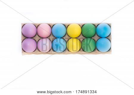 A dozen colored Easter eggs dyed lavender, pink, blue, yellow and green in a cardboard carton from above on a white background with copy space.