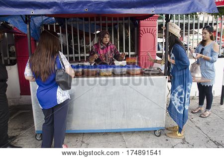 Travelers thai women and malaysian people buying rice topped malaysian curry style from local restaurant at beside Georgetown street on April 27 2016 in Penang Malaysia
