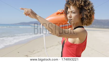 Lifeguard blowing a whistle on beach