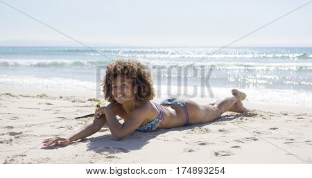 Smiling female sunbathing on beach