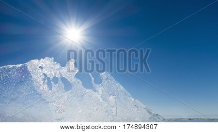 A transparent ice against the bright sun. Blue sky.