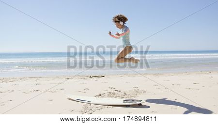Female listening music and jumping on beach