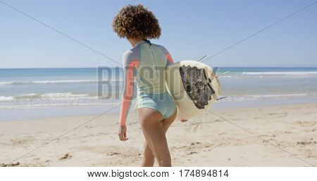 Female walking into sea to surf