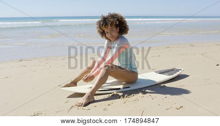 African woman sitting on surfboard