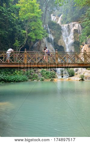 People On Bridge Looking And Take Photo With Viewpoint Of Kuang Si Falls