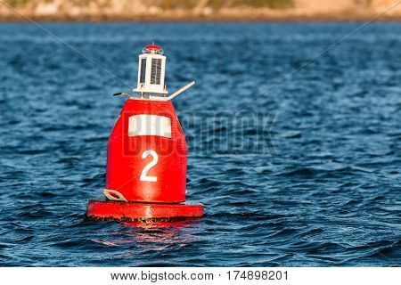 Red (Nun) companion buoy and boating channel marker in harbor.